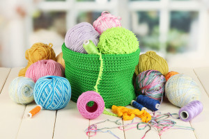 Colorful yarn for knitting in green basket on wooden table on window background